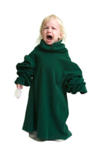 crying toddler in green shirt that's too big