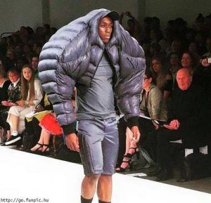 man with a large jacket walking on a fashion runway